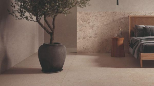 Rattan bed head and round wooden table against a marble effect tiled wall. There is a small olive tree in a large round container.