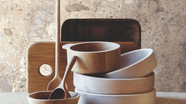 A selection of round wooded bowls with two wooden spoons in front of a beige marble wall tile.
